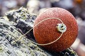 image of blown-up  - close up of orange Christmas bauble lying on a rock - JPG