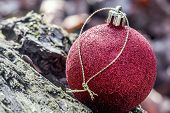 picture of blown-up  - close up of red Christmas bauble lying on a rock - JPG