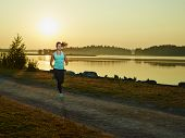 pic of morning  - Sporty fitness woman runs in the park early in the morning sunrise on the background - JPG