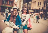 stock photo of scooter  - Multi ethnic girls on a scooter in european city - JPG
