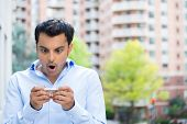 stock photo of jaw drop  - Closeup portrait funny young man shocked surprised wide open mouth by what he sees on his cell phone isolated outdoors building background - JPG