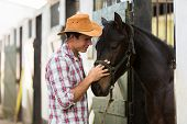 stock photo of stable horse  - young horse breeder comforting a horse in stable - JPG