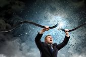 stock photo of tears  - Young businessman tearing electricity cable with hands - JPG