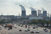 stock photo of fumes  - Rush hour traffic at the wide road opposite the fuming tubes of the thermal power station - JPG