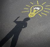 stock photo of lightbulb  - Childhood imagination and child creativity concept as the shadow of an inspired boy with a lightbulb chalk drawing on city asphalt as a symbol of inspiration and creative learning or back to school ideas - JPG