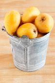stock photo of loquat  - loquat fruit in bucket on wooden table - JPG