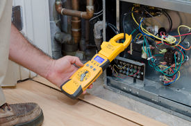 stock photo of electricity meter  - HVAC technician checking the amperage on a residential heat pump - JPG