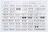 stock photo of protective eyewear  - exhibitor of glasses consisting of shelves of fashionable glasses shown on a wall at the optical shop