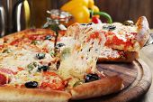 foto of hot fresh pizza  - Pizza with cheese on board and wooden table background - JPG
