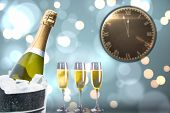 picture of count down  - Clock counting down to midnight against champagne cooling in ice bucket - JPG