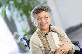 image of wheelchair  - Elderly woman in wheelchair reading book - JPG