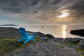 image of stratus  - Surreal looking picture of a blue chair contrasting with a very moody sky over the ocean in the background - JPG