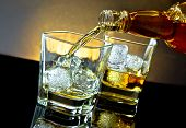 foto of whiskey  - barman pouring whiskey in front of whiskey glass on warm light and black table with reflection - JPG