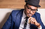 stock photo of cigar  - Young black man is wearing suit and hat smoking a cigar.