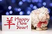 pic of sheep  - New Year Greeting card with white sheep toy the Chinese symbol of 2015 year on blurred lights background. Selective focus on sheep