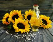 stock photo of sunflower-seeds  - Sunflower oil with sunflower seeds and flowers on a wooden table - JPG