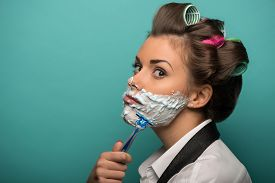 picture of gender  - Cute brunette woman in hair curlers playing fool with foam on face shaving with razor - JPG