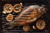 image of fried onion  - fried carp with lemon onion and spices on a black grill pan horizontal top view close - JPG