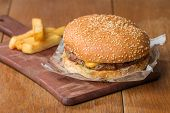 foto of beef-burger  - Delicious burger with beef tomato cheese and lettuce on paper and fries on wooden table - JPG