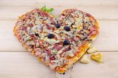 stock photo of olive shaped  - Heart shaped pizza on a wooden table - JPG