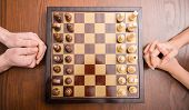 stock photo of chessboard  - Top view of two people are playing chess - JPG