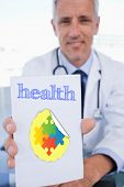 stock photo of prescription pad  - The word health and portrait of a male doctor showing a blank prescription sheet against autism awareness jigsaw - JPG