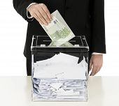 stock photo of ballot-paper  - Introducing envelope full of money in ballot box - JPG
