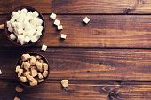 image of sugar cube  - White and brown sugar cubes in bowl on dark wooden background - JPG