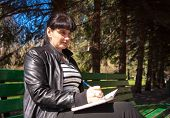 pic of black pants  - young beautiful woman in a black leather jacket and black pants sitting on a park bench writing a pen in notebook - JPG