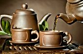stock photo of loam  - horizontal photo of the clay teapot tea flow in cup on brown background tea ceremony - JPG