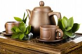 foto of loam  - still life of the clay teapot and cup on wooden trivet on white background isolated - JPG