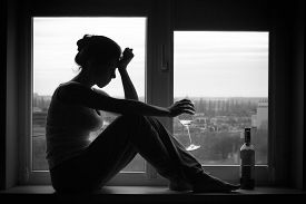 picture of sad  - Sad young woman sitting on the window drinks wine - JPG