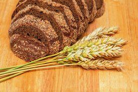 stock photo of malt  - Slices of rye malt bread and wheat ears on the chopping board - JPG