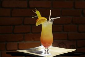 foto of vodka  - Glass with alcoholic sex on beach cocktail of vodka peach liqueur cranberry water orange juice and slice with green grapes and drink straws on white plate on brick wall background horizontal photo - JPG