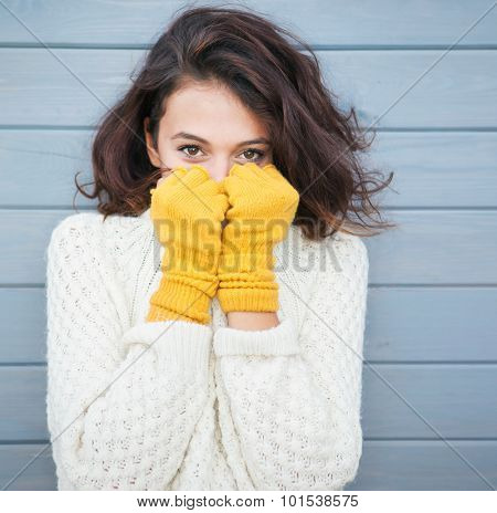 Beautiful natural young smiling brunette woman wearing knitted sweater and gloves. Fall and winter f