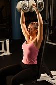 stock photo of weight-lifting  - female model working out in the gym lifting weights - JPG