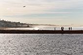 stock photo of lax  - taken with canon eos 300 35mm film camera early nov at beach in playa del rey. the silhoutte of the beach goers against the backdrop of the beach homes and plane taking off from lax  - JPG