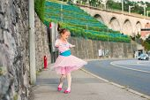 Постер, плакат: Outdoor portrait of a cute little girl of 7 years old walking to dance school
