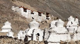 picture of karakoram  - Ruins of royal palace with white buddhist stupas in Tiger or Tiggur village in Nubra valley Ladakh Jammu and Kashmir India  - JPG