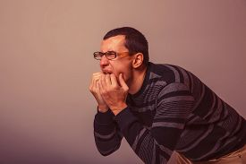 stock photo of vomiting  - male of European appearance dark hair stuck his hands in his mouth on a gray background - JPG