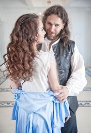 image of pompous  - Handsome man in medieval costume undress beautiful woman with long hair - JPG