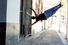 image of parkour  - Man doing parkour in the city on a sunny day - JPG