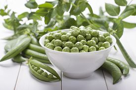 stock photo of pea  - Fresh green peas in a white bowl and some peas pods on a white table and branches of peas in the background - JPG