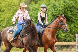 picture of cowgirls  - Active women western cowgirl and jockey training riding horse - JPG