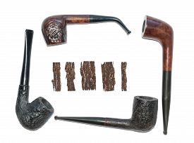 stock photo of tobacco-pipe  - four old wooden smoking pipes and pieces of pressed tobacco close - JPG