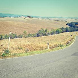stock photo of farmhouse  - Asphalt Road among Plowed Sloping Hills of Tuscany in the Autumn on the Background of Farmhouses in Italy Instagram Effect - JPG