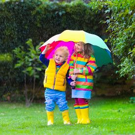 picture of rainy weather  - Little girl and boy with colorful umbrella playing in the rain - JPG