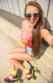 picture of roller-derby  - Smiling young woman in rollers is making selfie photo - JPG