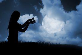 pic of moon silhouette  - Silhouette of woman zombie walking under full moon - JPG