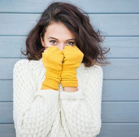 picture of shy woman  - Beautiful natural young smiling brunette woman wearing knitted sweater and gloves - JPG